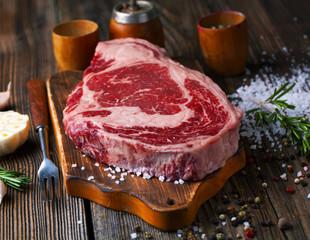 Raw ribeye steak marbled meat with salt, rosemary and garlic