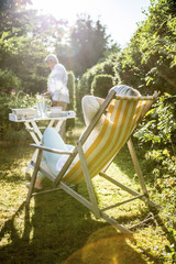 Mature woman relaxing in deckchair in garden with man in background