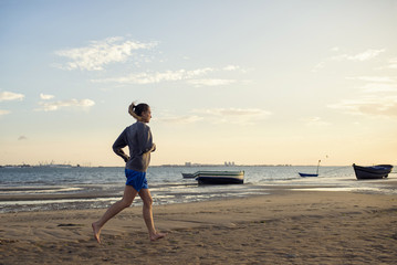 Spain, Puerto Real, woman jogging on the beach at evening twilight