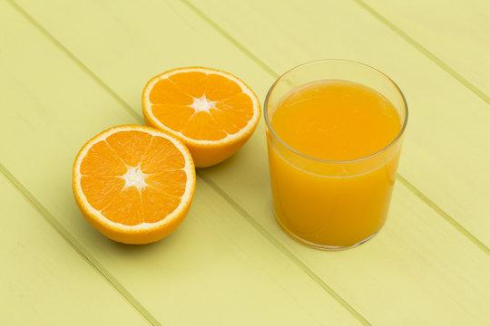 Orange juice and slices of orange on green table