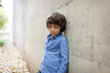 Portrait of sad little boy wearing denim shirt leaning against concrete wall