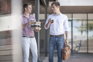 Colleagues talking in the street, holding coffee cups