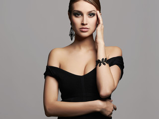 young beautiful sexy woman in black dress and jewelry.Beauty girl with make-up