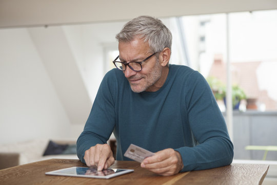 Mature man at home shopping online