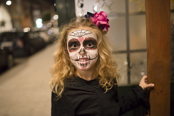 Blond little girl with sugar skull makeup at Halloween