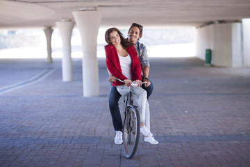Happy couple riding bicycle in parking garage