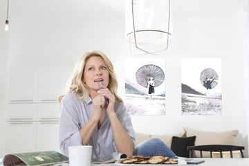 Woman sitting at the table in her living room thinking