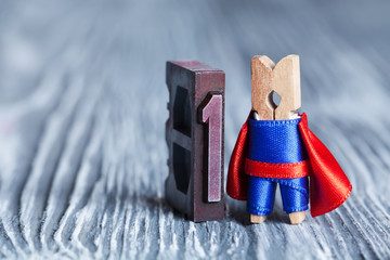 Leader concept. Clothespin superhero and 1 one written with colored vintage letterpress.  soft focus,