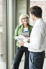 Portrait of smiling blond businesswoman communicating with a colleague