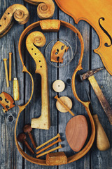Parts of the violin on wooden background