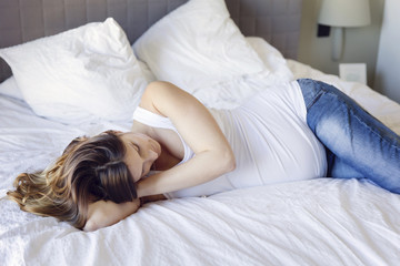 Pregnant woman relaxing on bed