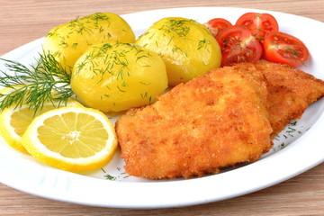 ryba smażona z ziemniakami i pomidorem