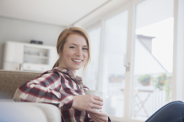 Portrait of smiling young woman relaxing with cup of coffee at home