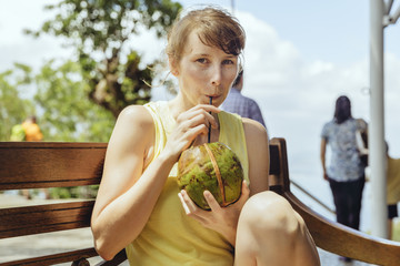 Woman drinking fresh coconut water from a coconut