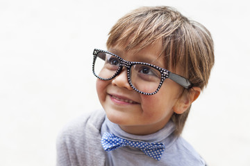 Portrait of smiling little boy wearing bow tie and oversized spectacles
