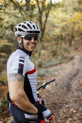 Portrait of smiling mountain biker withcycling helmet and sunglasses  in the forest