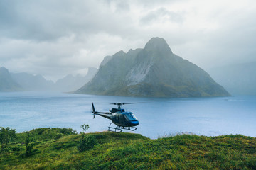 Helicopter in the great Norway mountains in cloudy weather. Reine, Lofotens