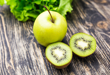 Fresh kiwi and apples   on wooden background. Concept of healthy lifestyle and healthy food. Selective focus. Rustic style.