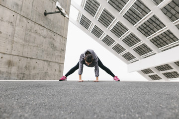 Spain, Barcelona, female jogger, stretching excersice under solar plant