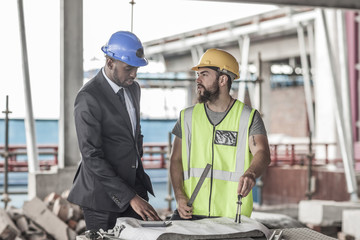 Construction worker and businessman discussing on construction site