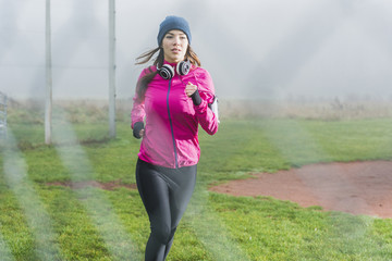Portrait of young woman jogging on a meadow behind mesh wire fence