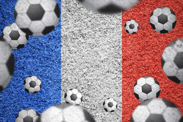Grunge textured soccer balls on a grass textured french flag. Football competition france textured flag with copy space background.
