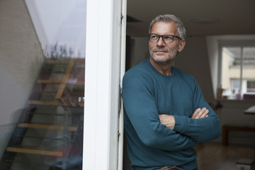 Mature man leaning against balcony door