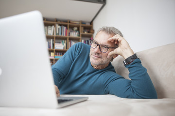 Mature man at home lying on couch using laptop
