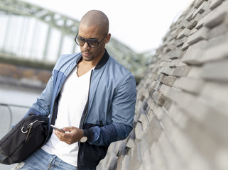 Germany, Cologne, Young man using smart phone