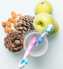 two colorful toothbrushes in a glass beaker with cones