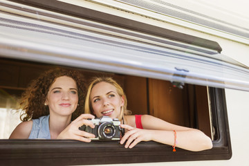 Two female friends with camera looking through window of caravan watching something