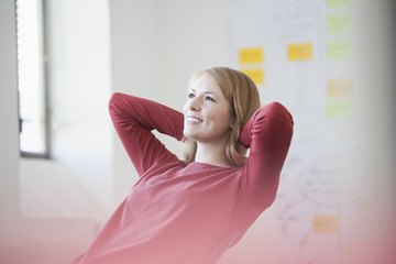 Young woman in office with hands behind head, daydreaming