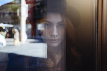 Portrait of young woman behind window pane