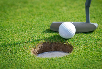Close-up of golf hole with putter and ball