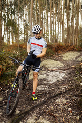 Mountain biker having a rest in the forest