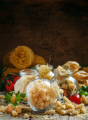 Dry Italian pasta spiraline in glass jars, selective focus