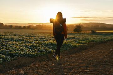 Spain, Catalunya, Girona, woman hiking on field path at sunrise
