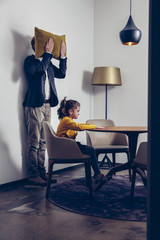 Girl sitting at table with father standing at a wall covering his face with a cushion