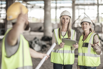Two women in protective workwear and construction worker in construction site