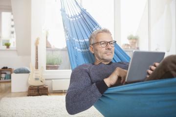 Mature man at home lying in hammock using digital tablet