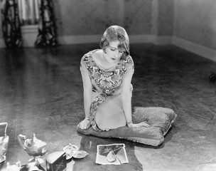 Woman kneeling on a pillow looking at a torn picture of a man