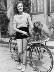 Woman next to her bicycle with her dog in the basket