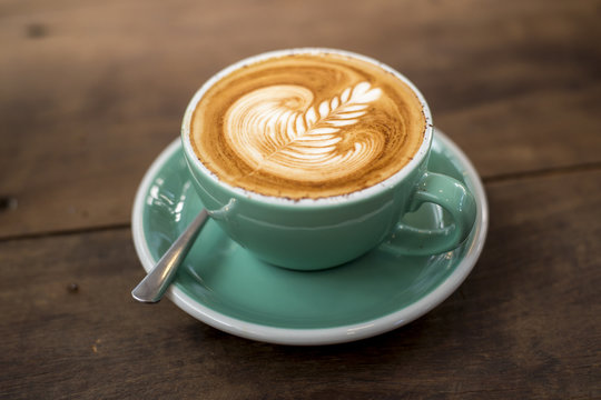 hot cappuccino with latte art on wood background