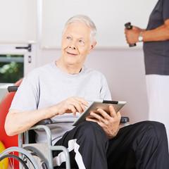 Alter Mann im Rollstuhl mit Tablet Computer