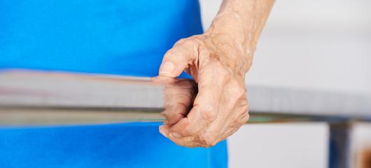 Faltige Hand einer Seniorin am Geländer