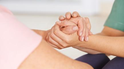 Krankenschwester hält Hände einer Senorin