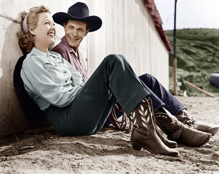 Laughing couple in western attire sitting on the ground