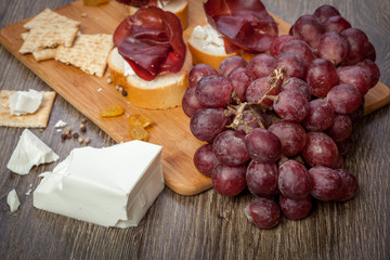 White cheese, ham, crackers and grape on wooden background