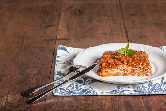 A slice of lasagna on a wood table