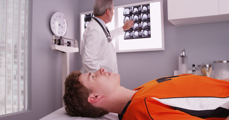 Portrait of young sports athlete lying down while doctor reviews